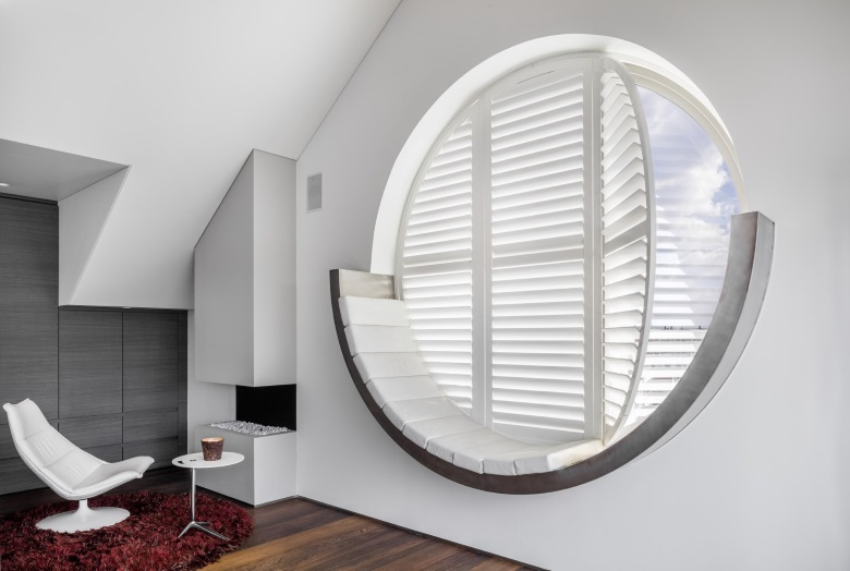 round white wooden shutters with white chair