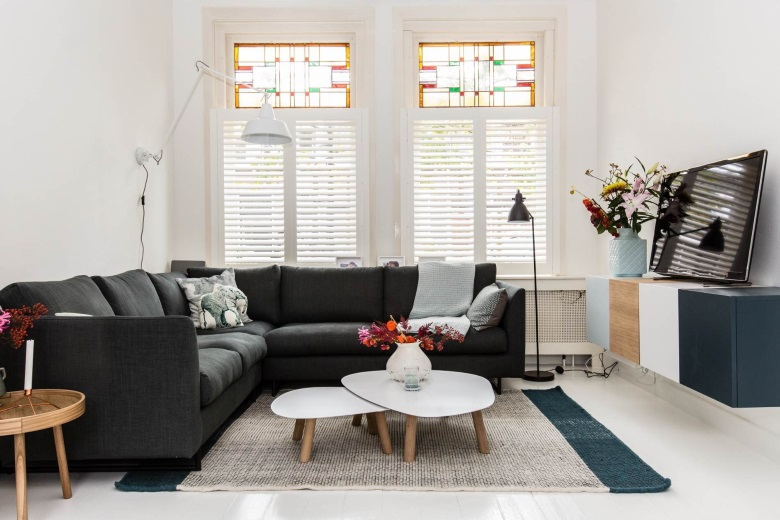 white wooden shutters in living room with stained glass